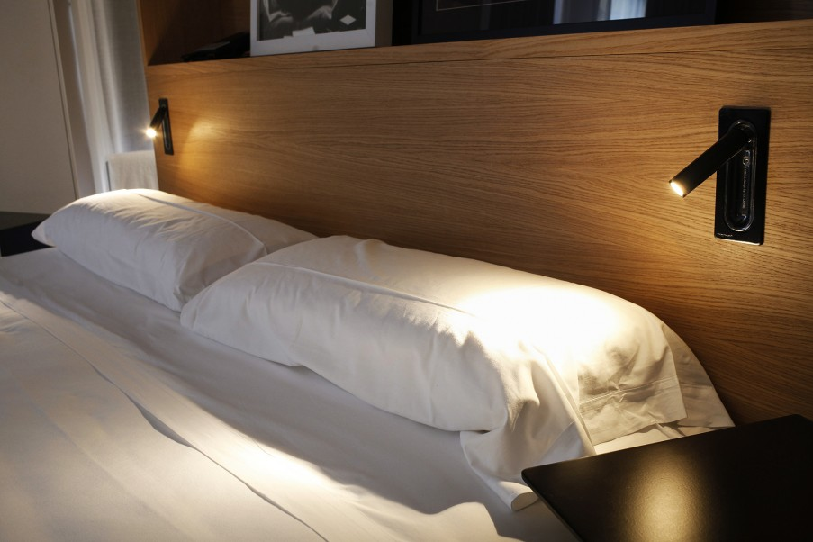 beweglicher schwarzer Wandstrahler am Bett schaltet beim einklappen