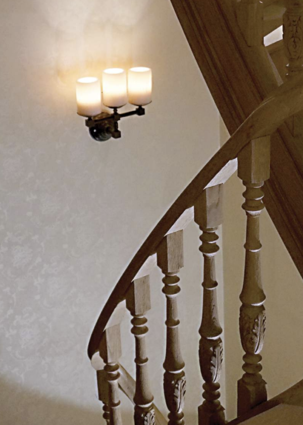 Harmonische Wandleuchte dreifach Kerzenoptik im Treppenhaus